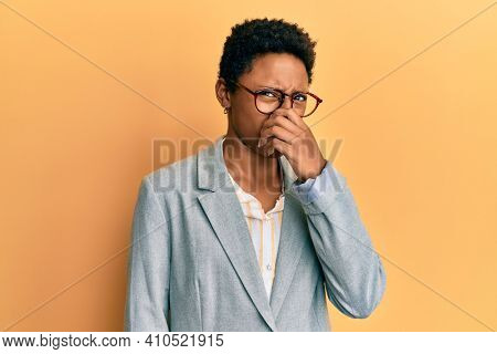 Young african american girl wearing business jacket and glasses smelling something stinky and disgusting, intolerable smell, holding breath with fingers on nose. bad smell