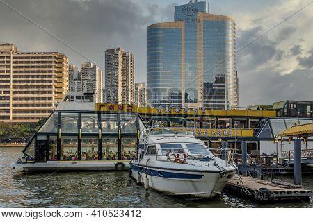 Guangdong, China - May 20, 2018: Moored Boat At A Jetty. Floating Restaurant Behind. Along The Pearl