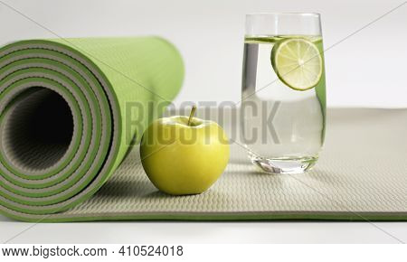 Yoga Fitness, Health Life Style. Yoga Rolled Green Mat , Green Apple, Glass Of Water With Lemon On W