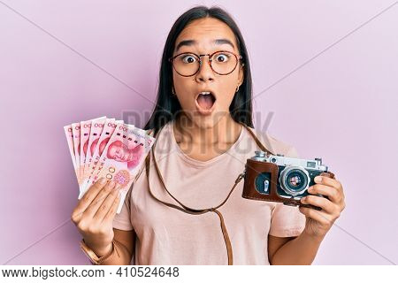 Young asian woman holding vintage camera and 100 chinese yuan afraid and shocked with surprise and amazed expression, fear and excited face.