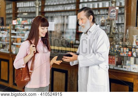 Experienced Professional Bearded Senior Man Pharmacist Holds Tablet And Consults Young Lady Customer