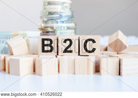 The Word B2c On The Wooden Blocks And A Bank With Money In The Background, Business Concept, B2c Sho