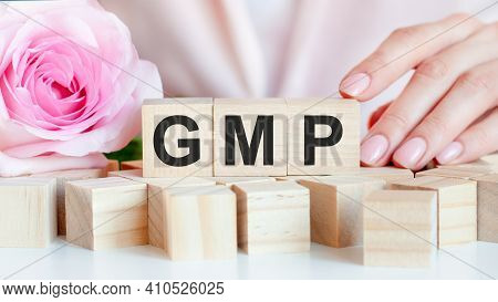 A Woman Holds A Wooden Cube With The Text Gmp In Her Hand. On The Wooden Cubes There Is A Living Ros