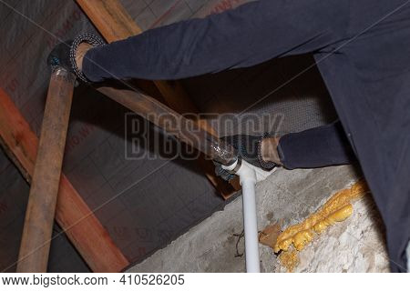 A Man Is Installing An Iron Pipe For A Solid Fuel Heating Boiler In A Private Country House.