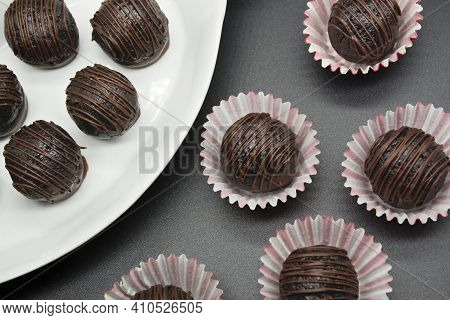 Chocolate Candy Truffles On Black Background Table, Top View. Homemade Dark Chocolate Truffles.
