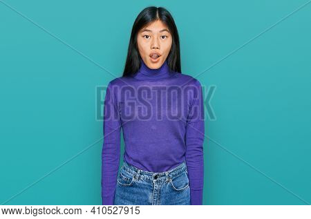 Beautiful young asian woman wearing casual clothes afraid and shocked with surprise and amazed expression, fear and excited face.