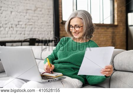 Happy Mature Businesswoman Accountant In Glasses And Green Jumper Sitting On The Couch With Laptop O