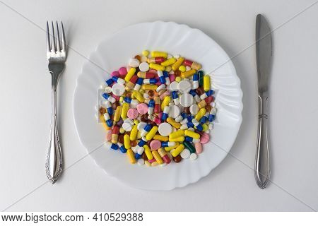 A Bunch Of Pills Lying On A Plate, Next To A Fork And A Knife