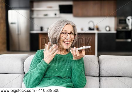 Mature Lady Businesswoman Grandmother With Gray Hair In Green Jumper, Sitting On The Couch In The Li