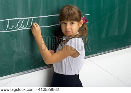 Serious Schoolgirl Standing At Blackboard. Portrait Of Elementary School Student Girl In White Blous
