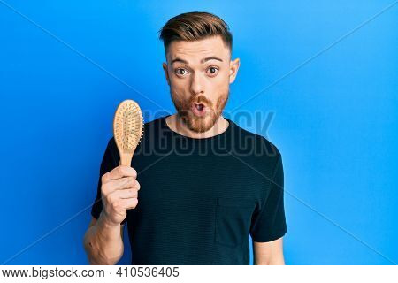 Young redhead man holding hairbrush scared and amazed with open mouth for surprise, disbelief face