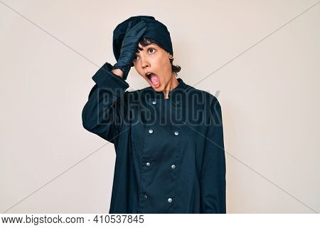 Beautiful brunettte woman wearing professional cook uniform surprised with hand on head for mistake, remember error. forgot, bad memory concept.