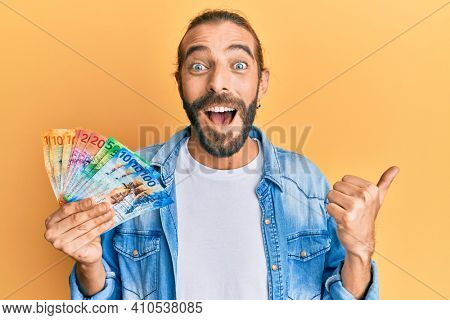 Attractive man with long hair and beard holding swiss franc banknotes pointing thumb up to the side smiling happy with open mouth