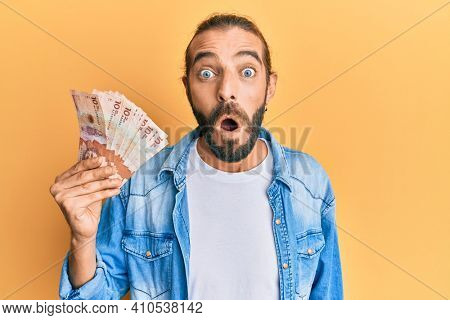 Attractive man with long hair and beard holding 10 colombian pesos banknotes scared and amazed with open mouth for surprise, disbelief face
