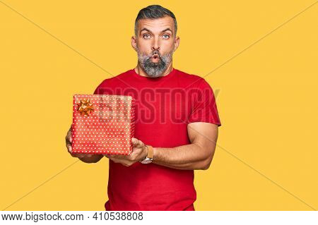 Middle age handsome man holding gift scared and amazed with open mouth for surprise, disbelief face