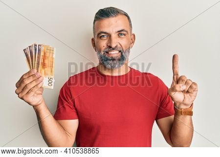 Middle age handsome man holding 500 norwegian krone banknotes smiling with an idea or question pointing finger with happy face, number one