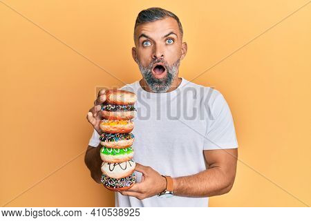 Middle age handsome man holding tasty colorful doughnuts afraid and shocked with surprise and amazed expression, fear and excited face.