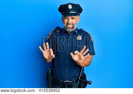 Middle age handsome man wearing police uniform disgusted expression, displeased and fearful doing disgust face because aversion reaction.