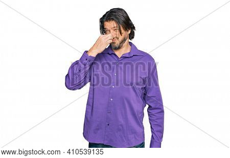 Middle age handsome man wearing business shirt smelling something stinky and disgusting, intolerable smell, holding breath with fingers on nose. bad smell