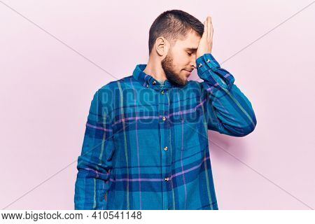 Young handsome man wearing casual shirt surprised with hand on head for mistake, remember error. forgot, bad memory concept.
