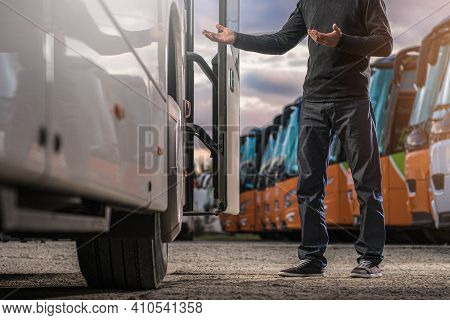 Caucasian Bus Driver In His 40s Welcoming Passengers While Staying And Welcoming Next To Tour Bus Do