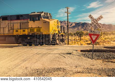 Southern California Mojave Desert Railroad Crossing In Rural Place. Cargo Train Engine. Railroad Tra