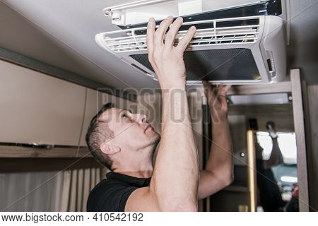 Caucasian Rv Appliances Technician In His 40s At Work. Looking For Potential Issue With Air Conditio