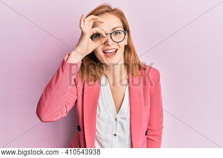 Young caucasian woman wearing business style and glasses doing ok gesture with hand smiling, eye looking through fingers with happy face.
