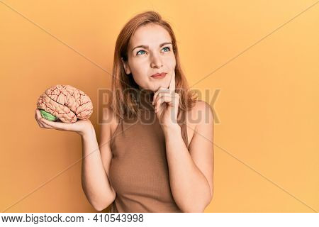 Young caucasian woman holding brain serious face thinking about question with hand on chin, thoughtful about confusing idea