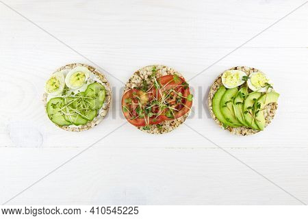 Toasts With Egg, Avocado, Micro Greens, Cucumbers And Tomatoes On A White Wooden Background. Healthy