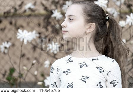 Little Girl On Floral Blossom In Spring. Child With Blossoming Flowers Outdoor. Beauty Kid With Fres