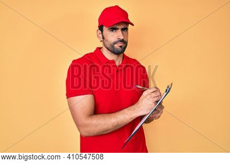 Handsome hispanic delivery man with beard checking list of deliveries skeptic and nervous, frowning upset because of problem. negative person.