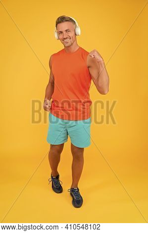 Regular Workout. Mature Coach. Strong Sportsman Wear Headphones And Fitness Uniform. Healthy Sportsm