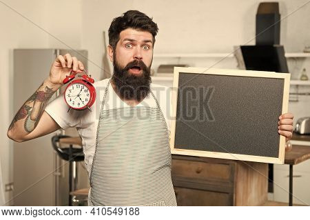 Male Housekeeper In Kitchen. Cooking By Recipe. Bearded Hipster Offer Menu. Restaurant Staff. Copy S
