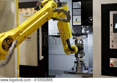 Robotic Arm Loads A Workpiece Into The Cnc Machine. Selective Focus.