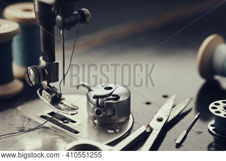 Close Up On Metal Shuttle, Foot Of Vintage Sewing Machine, Scissors, Spool Of Thread, Sewing Needles