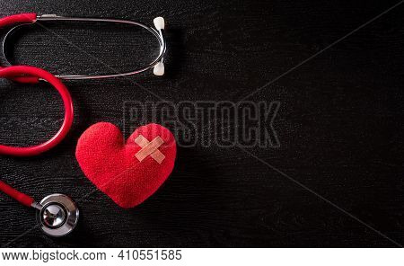 Top View Of Red Heart With Doctor Physician's Stethoscope On Dark Stone Background. Hospital Life In