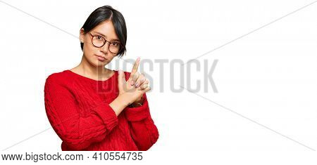 Young beautiful hispanic woman with short hair wearing casual sweater and glasses holding symbolic gun with hand gesture, playing killing shooting weapons, angry face