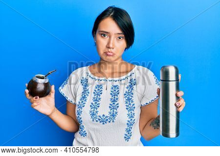 Beautiful young woman with short hair drinking mate infusion depressed and worry for distress, crying angry and afraid. sad expression.