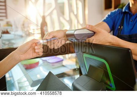 Hands Of Female Customer Giving Credit Card To Barista When Paying For Coffee In Coffeeshop