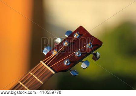 Guitar Tuner. Wooden Guitar On A Natural Blurred Background. Guitar Tuning. The Guy Tunes The Guitar