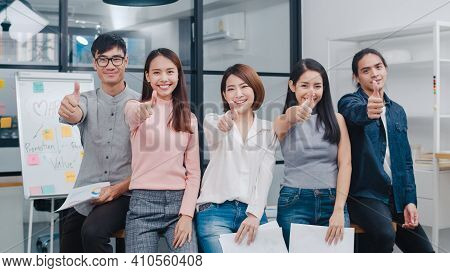 Group Of Asia Young Creative People In Smart Casual Wear Smiling And Thumbs Up In Creative Office Wo