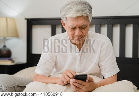 Asian Senior Men Using Mobile Phone At Home. Asian Senior Chinese Male Search Information About How