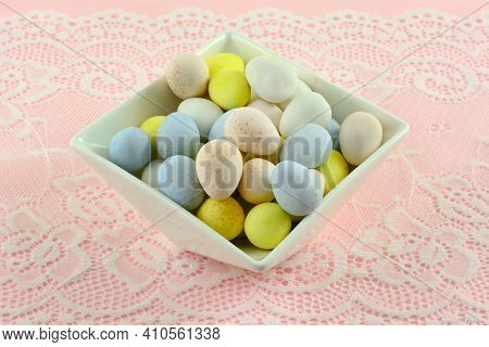 Pastel Colored Candy Easter Eggs In White Dessert Bowl  On White Lace On Pink Background