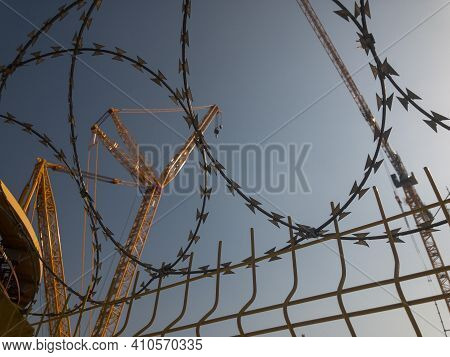 Construction Site With Huge Yellow Lifting Crane Opposite Blue Sky Surrounded By Barbed Wire Fence.