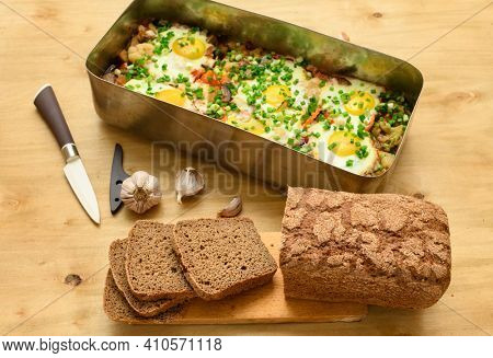 rye bread, baked mixed vegetables and eggs close view, baking tray with tomatoes, broccoli and spices, home cooking