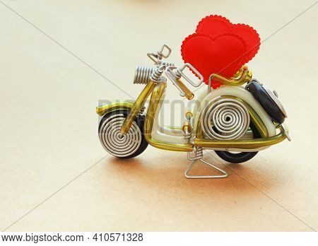 A Red Heart On A Toy Motorcycle On Craft Paper Background. Concept Love, Greeting Card, Banner, Post