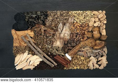 Traditional Chinese fundamental herb collection most frequently used in herbal medicine on black wood background. Flat lay. Top view.