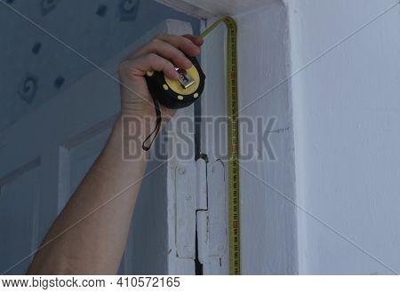Hand Measuring The Height Of The Doorway Using A Yellow Tape Measure In Taking Measurements, Prepari
