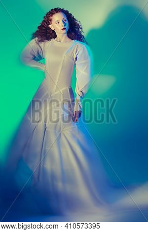 Full length portrait of a refined fashion model girl with lush red curly hair posing in a long white haute couture dress. Studio shot. Art and fashion.